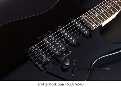 Black electric guitar close up on dark background.