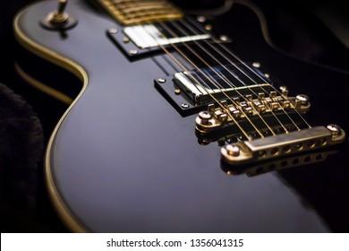 Black electric guitar closeup on dark background