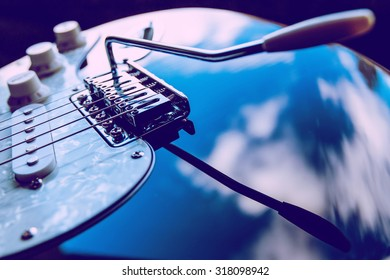 Black electric guitar and clouds. Focus point is on the front of bridge. Image includes a effet.