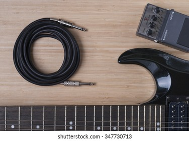 black electric guitar and distortion unit on a wooden background texture
