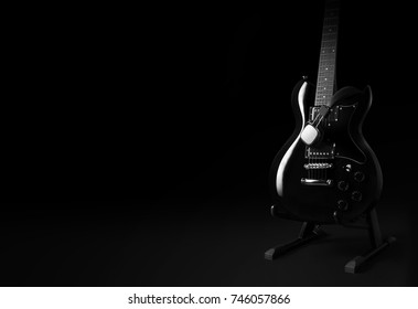 black electric guitar and headphone on black background concept