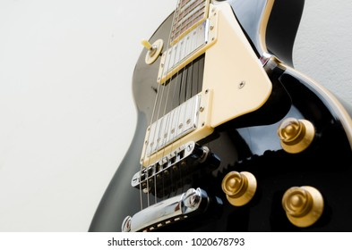 black electric guitar on a white background showing part of the body in a bottom and close view