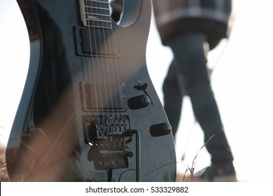 Black electric guitar with person walking behind in the background. Concept: Heavy Metal, Emo, Rock, Music