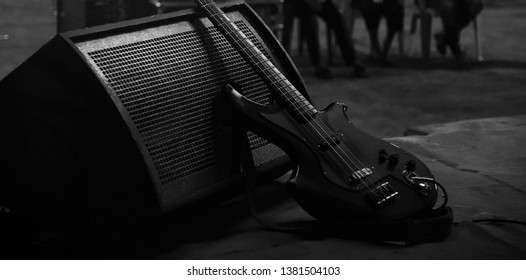 A black electric guitar with a speaker on a stage of a concert
