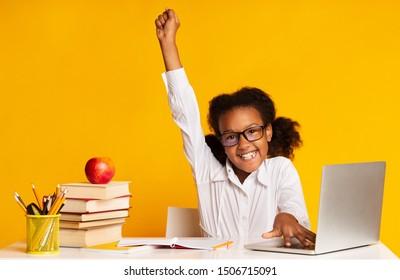 Black Elementary Student Girl Raising Hand Sitting At Laptop Doing Homework Over Yellow Background. Studio Shot