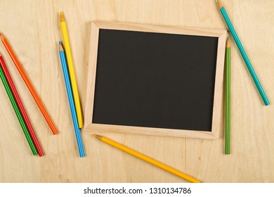 Black, empty, blank chalkboard with colored pencils on brown wooden desk flat lay from above with copy space