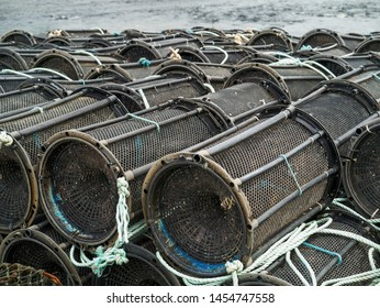 Black empty fish and crab traps ashore, Water in the background. Fishing industry.