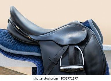 Black English saddle hanging on fence near stables. Side view.