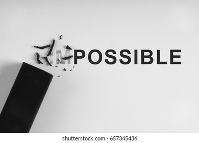 "Black eraser on white paper erase letters ""IM"" from the word IMPOSSIBLE into POSSIBLE"