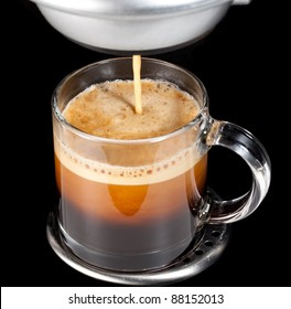 Black espresso coffee with heady froth in a glass mug or cup