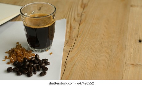 The black espresso shot in the glass cup with its ingredients, brown rock sugar and roasted coffee bean on the white paper, all is on the wooden desk as work space