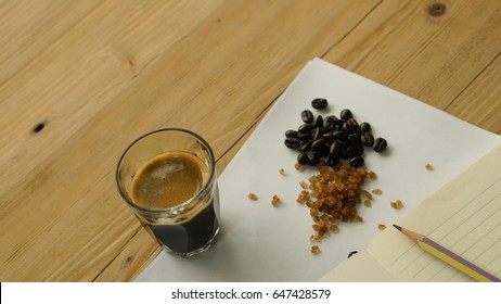 The black espresso shot in the glass cup with its ingredients, brown rock sugar and roasted coffee bean on the white paper, all is on the wooden desk with note and pencil like work space