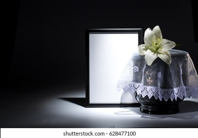 Black evangelical urn with blank mourning frame, and Lilly flower on dark background