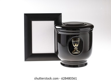 Black evangelical urn with blank mourning frame, and flower on bright background