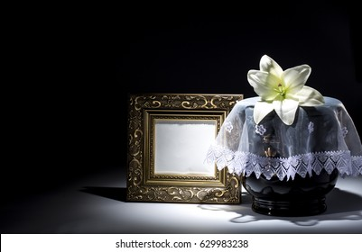 Black evangelical urn with blank mourning frame and lilly flower