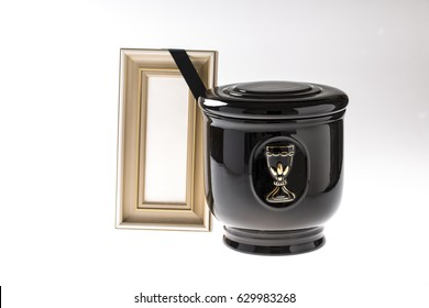 Black evangelical urn with blank mourning frame on bright background