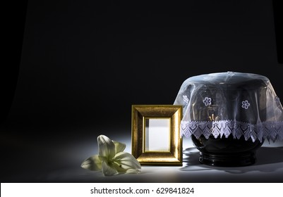 Black evangelical urn with golden mourning frame, and flower on dark background