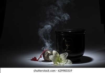 Black evangelical urn with with incense, and white flower