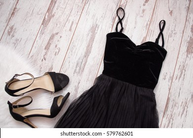 Black evening dress and shoes on a wooden background. Fashion concept. Top view, space for text