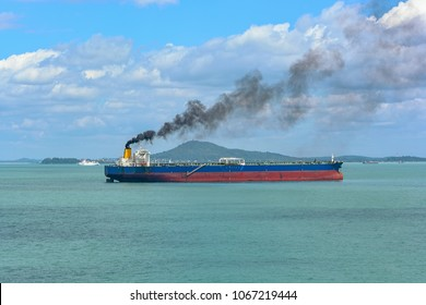 Black exhaust fumes coming from the chimney of an moored tanker after main engine ignition.
