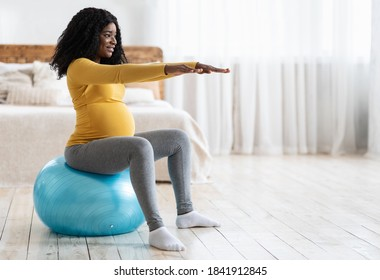 Black expecting woman training on ball, getting ready for childbirth. Smiling african pregnant lady with big tummy sitting on fitness ball in bedroom, looking at copy space. Sport during pregnancy