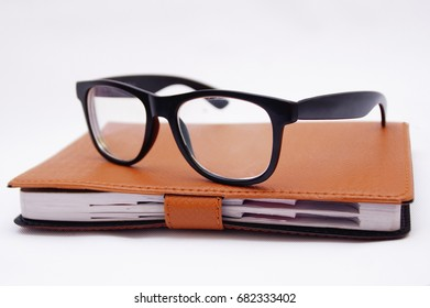 Black Eye Glasses On Bussiness Management Book Over White Background