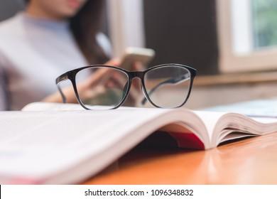 black eye glasses on white book on the desk, warm tone, education concept