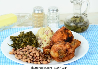 Black eyed peas and turnip greens with deep fried chicken legs and potatoes and spicy vinegar sauce on blue gingham place mat.  Southern cooking where dinner is often called supper.