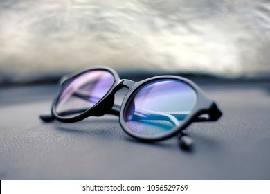 Black eyeglasses on black table and blur glass window with rain in background.