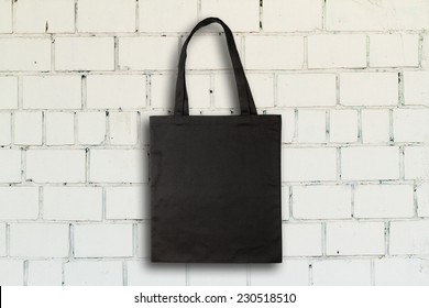 Black fabric bag against vintage brick wall