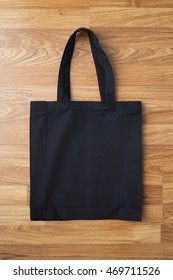 Black fabric bag on wooden background