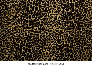 Black fabric with metallic golden leopard fur print. Retro fashion background.