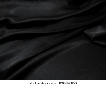 Black fabric texture background, wavy fabric slippery black color, luxury satin cloth texture.