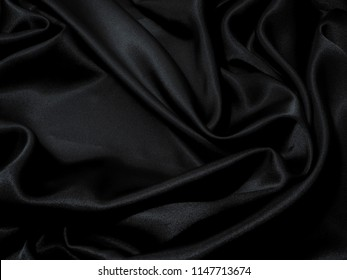Black fabric texture background, wavy fabric slippery black color, luxury satin cloth texture