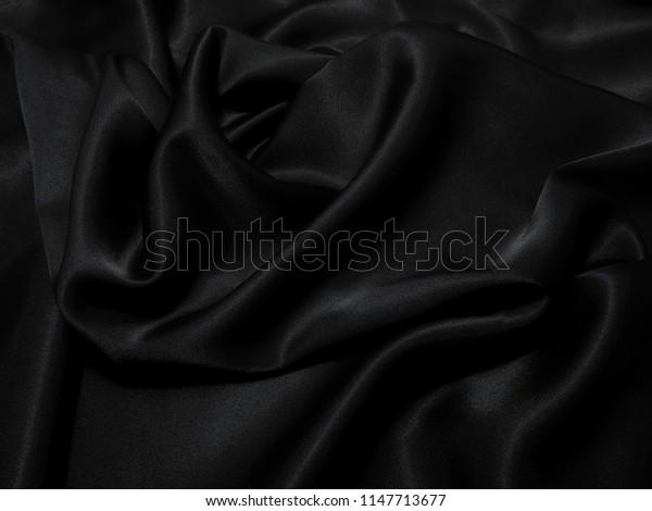 Black fabric texture background, wavy fabric slippery black color, luxury satin cloth texture