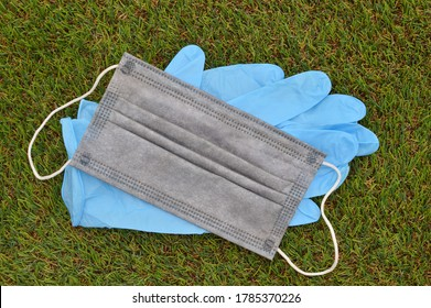 Black Face mask and Blue Latex Gloves on green grass