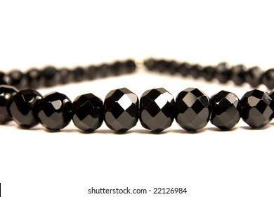 black faceted gems against white background