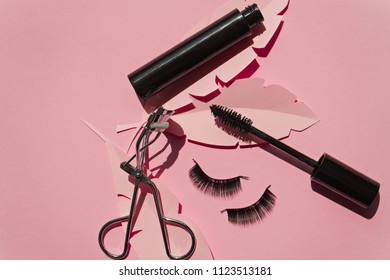 Black false lashes strips,mascara, curler on pink background