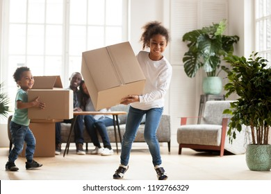 Black family in living room at new home. Happy parents sitting on couch looking at children, preschool daughter toddler son playing carrying cardboard boxes. New house, buying property, moving concept