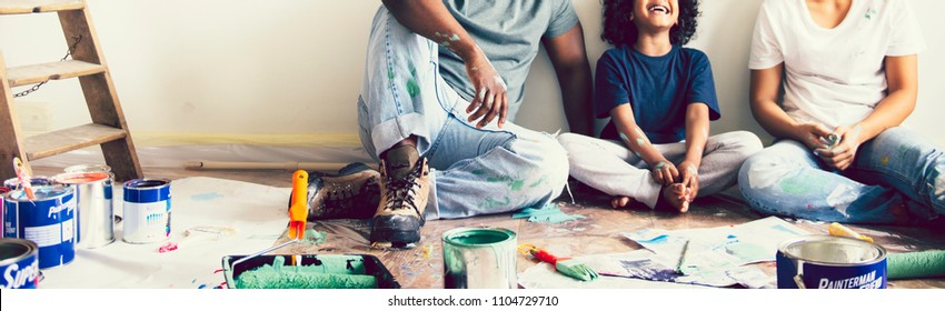 Black family painting the house wall