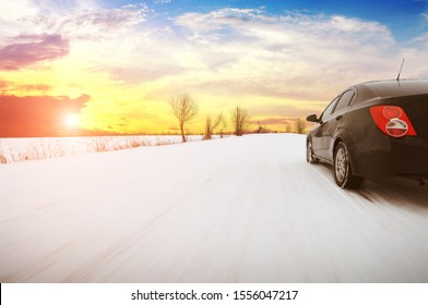 Black family sedan car driving fast on the winter countryside road with snow against a night sky with a sunset