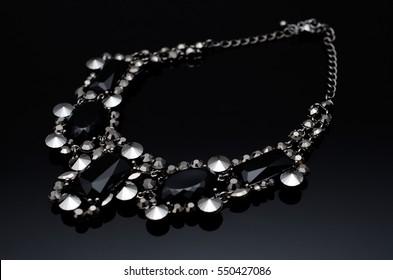 Black fashion luxury necklace on black background