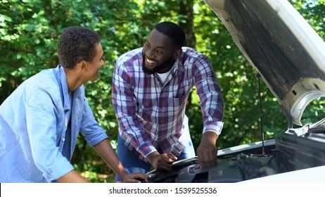Black father explaining car structure to son and smiling, teamwork, family