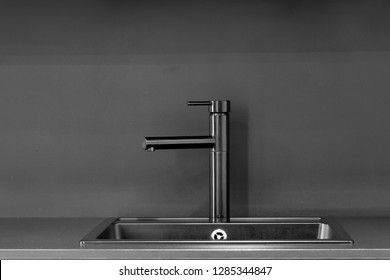 Black faucet with black sink, black table top and black wall