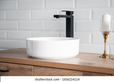 Black faucet for water and white separate high sink on wooden pedestal. Loft style bathroom.