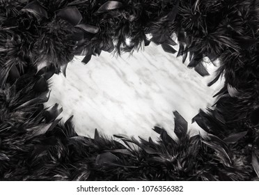 Black feather frame on marble background, with copy space.