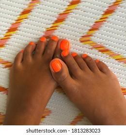 Black Feet crossed on brightly colored rug
