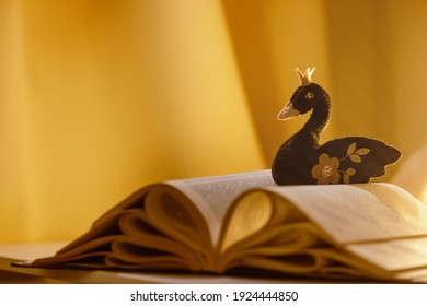 A black felt handmade swan with a  crown  lies on an open book. The concept of animated fairy tales and stories, reading is a different reality.