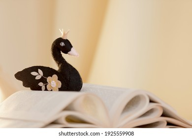 A black felt handmade swan with a  crown  lies on an open book. The concept of animated fairy tales reading and stories, reading is a different reality, hobby.