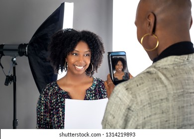 Black female actress doing a self tape audition via cell phone camera in a studio while reading to a casting director.  Depicts the Hollywood entertainment industry process.